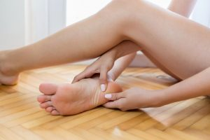 Woman massaging her aching foot